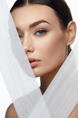 Face Skin Beauty. Beautiful Woman With Natural Makeup, Healthy Skin With White Pieces Of Fabric. High Resolution.