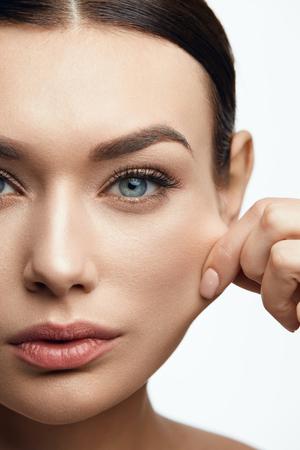 Healthy Skin. Beautiful Woman With Beauty Face Pulling Elastic Facial Skin. High Resolution. Foto de archivo