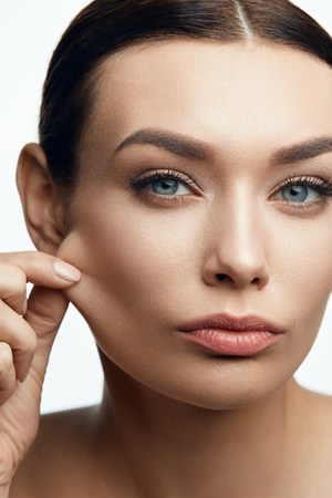 Elastic Skin. Woman With Beautiful Face And Natural Makeup Pulling Skin. High Resolution.