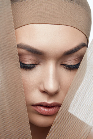 Skin Care Beauty. Woman With Beautiful Face, Natural Makeup And With Beige Fabric. High Resolution. Foto de archivo