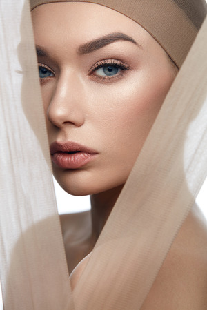 Skin Care Beauty. Woman With Beautiful Face, Natural Makeup And With Beige Fabric. High Resolution. Banco de Imagens