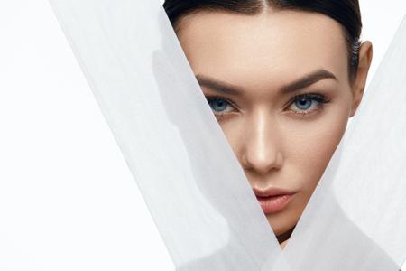 Gesicht Haut Schönheit. Schöne Frau mit natürlichem Make-up, gesunde Haut mit weißen Stücken Gewebe. Hohe Auflösung. Standard-Bild