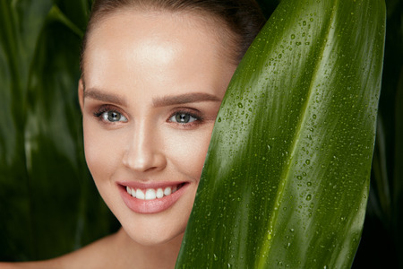 Natural Skin Beauty. Beautiful Woman With Healthy Face Holding Green Leaf On Jungle Background. High Resolution. Stockfoto