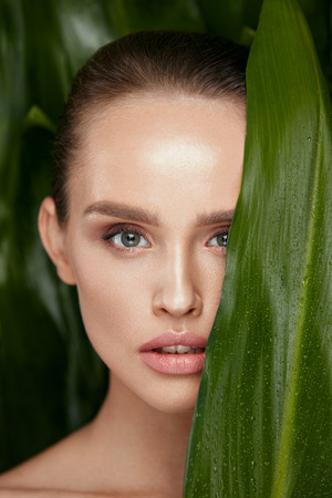 Skin Care. Beautiful Woman With Natural Makeup And Healthy Facial Skin Holding Green Leaves. High Quality Image. Фото со стока