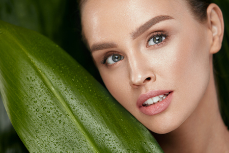 Beauty Woman Face With Healthy Skin And Natural Makeup With Green Plant On Jungle Background. High Resolution.
