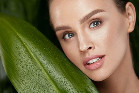 Visage de femme de beauté avec une peau saine et un maquillage naturel avec des plantes vertes sur fond de jungle. Haute résolution.