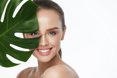 Facial Beauty. Beautiful Woman With Fresh Healthy Skin Holding Green Plant On White Background. High Resolution. Banque d'images