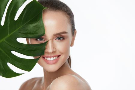 Belleza Facial Mujer hermosa con la piel sana fresca que sostiene la planta verde en el fondo blanco. Alta resolución.