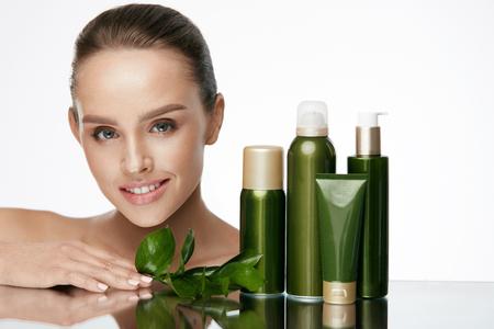Beautiful Woman With Natural Makeup And Organic Skin Care Cosmetics On White Background. High Resolution. Stock Photo