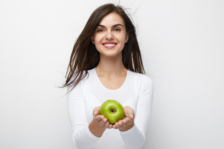 Woman With Green Apple. Beautiful Smiling Female With White Smile Holding Fruit. High Quality