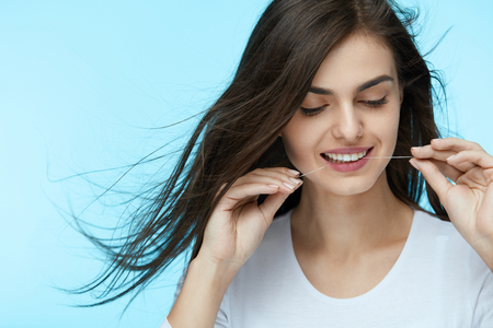 Dental Care. Beautiful Woman Flossing, Cleaning Healthy White Teeth With Tooth Floss On Blue Background. High Quality 写真素材