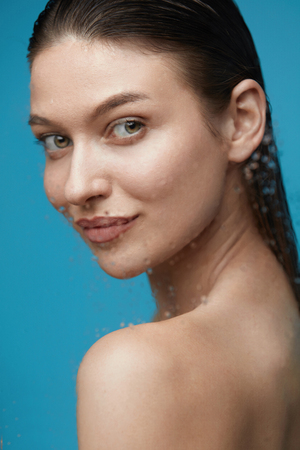 Woman In Shower. Beautiful Female With Wet Hair, Beauty Face And Fresh Skin On Blue Background. High Quality Imagens