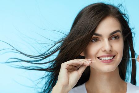 Cuidado dental. Hermosa mujer hilo dental, limpieza de dientes blancos sanos con hilo dental sobre fondo azul. Alta calidad