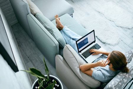 Young Man With Laptop At Home. Handsome Male Wearing Home Clothes Working At Computer, Sitting On Sofa. High Resolution. Stock Photo