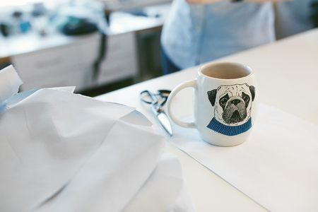 Cup Of Coffee On Tailors Table In Atelier. Close Up Of Mug With Funny Dog Face Print On It Standing On Table In Clothes Designers Working Environment. Stock Photo