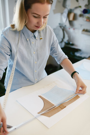 Female Tailor With Tape Measuring Sewing Pattern On Table In Atelier. Dog Clothes Designer Working With Paper Pattern In Workplace.
