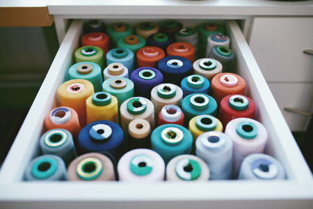 Close Up Of Colorful Sewing Threads In Drawer. Closeup Shot Of Multicolored Spools Of Thread, Sewing Accessories In Atelier.