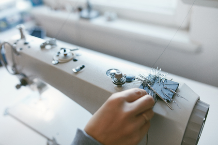 Close Up Of Female Working On Sewing Machine. Tailor Hands Taking Needles And Pins From Magnet On Top Of Sewing Machine Stock Photo