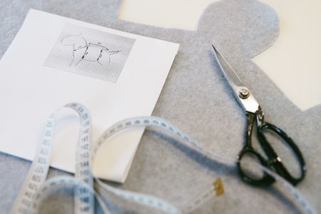 Tailors Tools On Tailors Table. Close Up Shot Of Sewing Supplies Such As Scissors, Measuring Tape, Fabric Pattern And Dog Body Measurements Lying On Table In Pet Atelier
