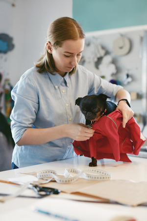 Dog Clothes. Female Tailors Wearing Bright Red Suit On Pet On Table In Atelier.