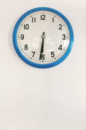 Close Up Of Blue Clock Hanging On White Wall Showing Half Past Six 写真素材