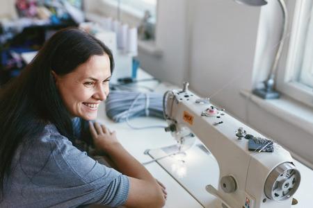 Wijfje dat aan de naaimachine werkt. Portret Van Vrouw Kleermaker Naaien Kleren Zittend Aan Tafel