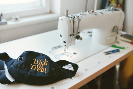 Close Up Of Sewing Machine And Waist Bag With Halloween Inscription On It Lying On Tailors Table In Pets Atelier.