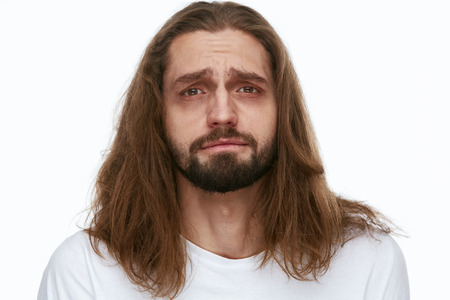 Tired Man With Exhausted Face And Dark Circles Under Eyes And Long Hair On White Background. High Resolution. Stock Photo