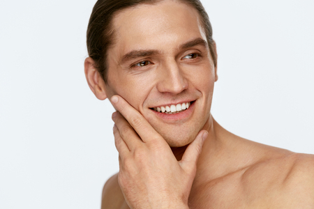 Men Face Care. Man Touching Smooth Skin After Shaving On White Background. High Resolution. Stock Photo
