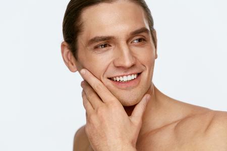 Uomini Face Care. Uomo che tocca la pelle liscia dopo la rasatura su priorità bassa bianca. Alta risoluzione.