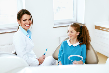 Dental Health. Female Dentist And Little Happy Girl Sitting In Dentistry Office. High Resolution.