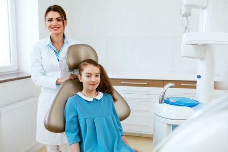 Dentistry. Female Dentist Doctor And Little Patient In Light Dental Clinic. High Resolution. Stok Fotoğraf