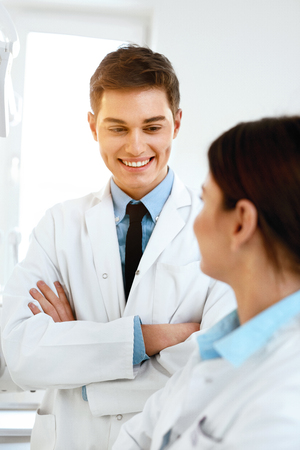 Male Dentist In Dental Clinic. Portrait Of Happy Dentistry Doctor Wearing White Coat. High Resolution.