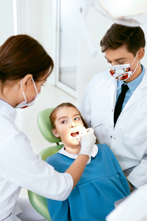 Oral Health Care. Dentist Doctors Making Examination Procedure For Little Girl In Dentistry Clinic. High Resolution.