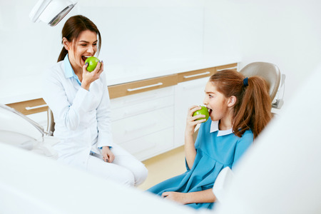 Dental Clinic. Female Dentist And Little Patient Eating Green Apple In Dentistry Office. High Resolution. Stok Fotoğraf