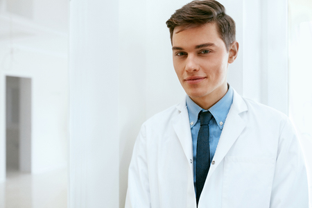 Male Dentist Doctor In Dental Clinic. Portrait Of Happy Dentistry Doctor Wearing White Coat. High Resolution. Stock Photo