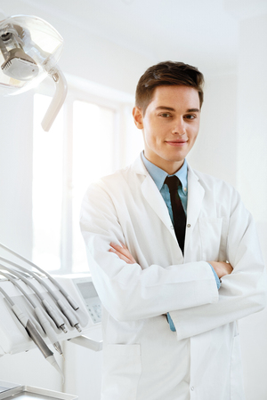 Male Dentist In Dental Clinic. Portrait Of Happy Dentistry Doctor Wearing White Coat At Workplace. High Resolution. Stock Photo