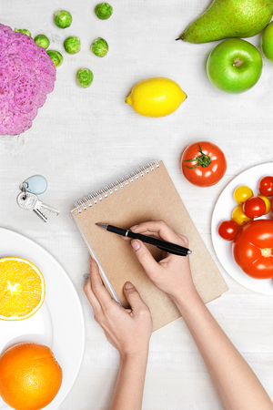 Healthy Food. Woman Hand Writing Diet Plan On Paper, With Vegetables And Fruits On White Table. High Resolution