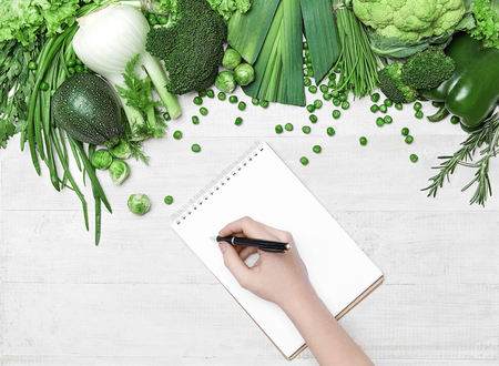 Diet Plan. Female Hand Writing In Notebook Near Fresh Green Vegetables On White Table. High Resolution. Stock Photo