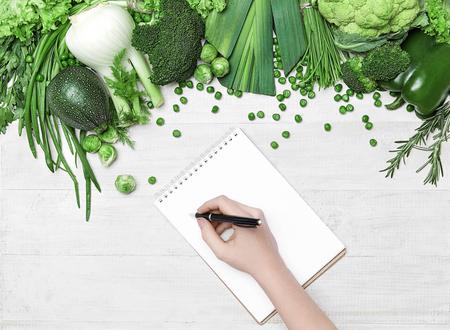 Plan diety. Ręka Pisania W Notatniku W Pobliżu Świeżych Zielonych Warzyw Na Białym Stole. Wysoka rozdzielczość.