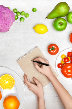 Nutrition Diet Food. Woman Writing Product Plan On Paper With Vegetables And Fruits On White Table. High Resolution