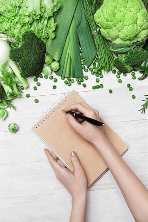 Diet Plan. Female Hand Writing In Notebook Near Fresh Green Vegetables On White Table. High Resolution. Reklamní fotografie
