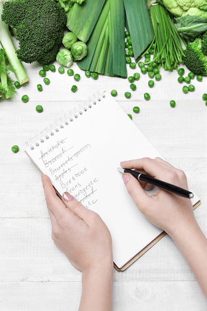 Shopping List. Hand Writing In Notebook Near Fresh Green Vegetables On White Table. High Resolution. Stock Photo
