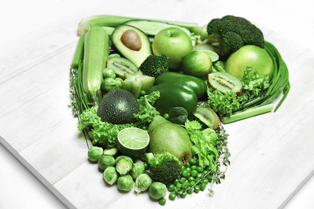 Heart Of Green Vegetables And Fruits On White Wooden Background. High Resolution. Stock Photo