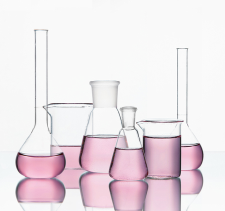Laboratory Supplies. Transparent Glassware With Colorful Chemical Liquid On White Background. High Resolution.