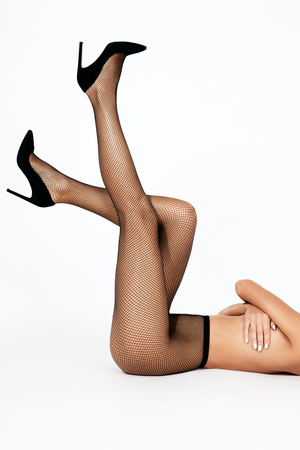 Sexy Long Female Legs In Black Fashion Fishnet Tights And High Heels Shoes On White Background. High Resolution. Stock Photo