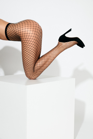 Sexy Long Female Legs In Black Fashion Fishnet Tights And High Heels Shoes On White Background. High Resolution. Zdjęcie Seryjne