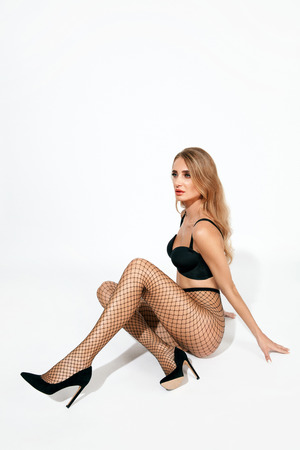 Sexy Woman In Black Fishnet Tights. Beautiful Female With Fit Body In Stockings On Long Legs. High Resolution. Stock Photo