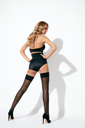 Stockings. Back View Of Sexy Young Blonde Female With Long Sexy Legs Wearing Black Underwear. High Resolution.