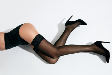 Woman Long Slender Legs In Black Sexy Stockings On White Background. High Resolution.